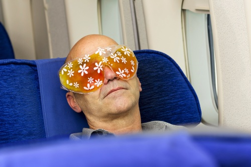 Mann mit Augenschutz schläft im Flugzeug
